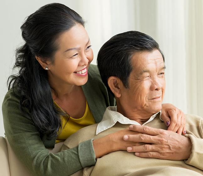 Happy embracing mature couple looking through the window