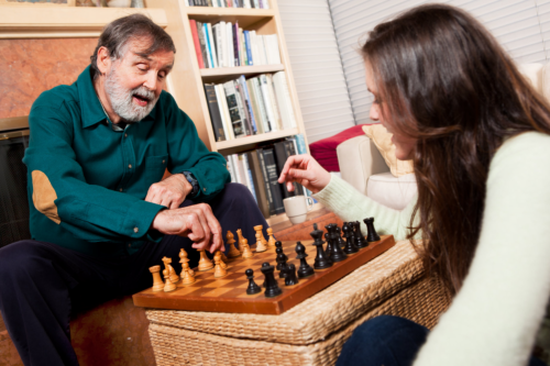 elderly man and her caregiver playing chess